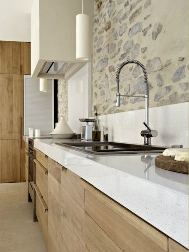Kitchen with a cohesive mix of textures and neutrals with good lengths of stone counter top space, chrome fixtures, wood cabinetry, rougher stone on accent walls