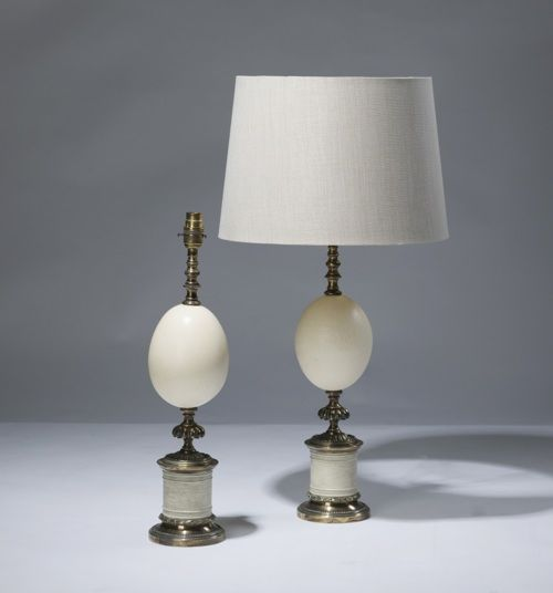 pair of medium cream ostrich egg lamps on distressed brass bases