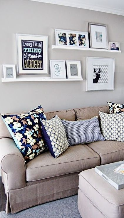 above the couch simple plank floating shelves uses large frames mounted on the wall an small picture frames propped up on the shelves