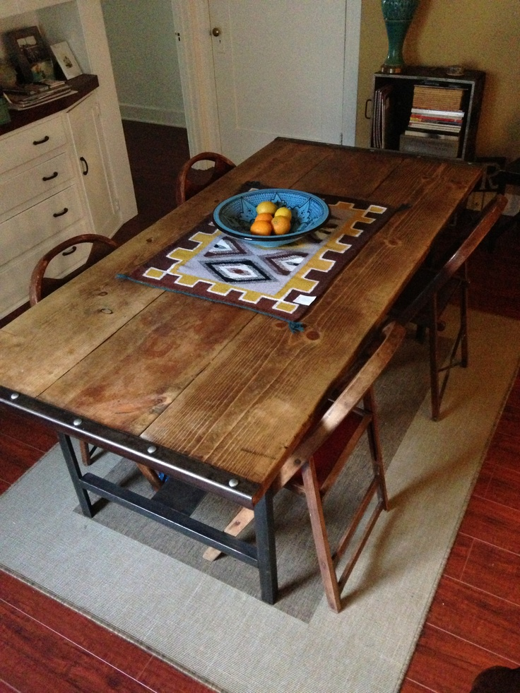 Dining room table, folding chairs, southwestern tapestry.