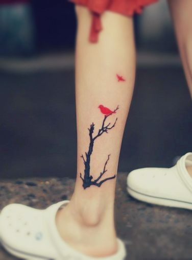 A tattoo featuring a red bird resting on a black tree and another bird flying away I would love to get this in remembrance of my granny, she loved cardinals