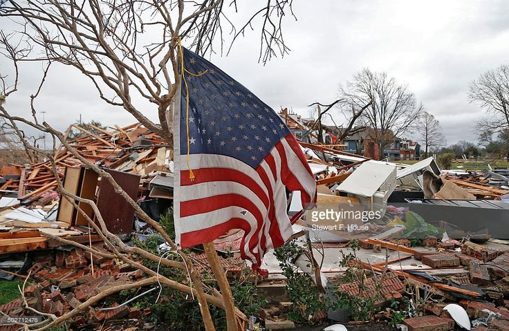 A tattered U.S. flag that had been attatched to a tree waves over the debris at the Landmark at Lake Village North Apartments as the recovery process begins following tornadoes which hit the area late Saturday night December 28, 2015 in Garland, Texas. A meteorolocical assault of tornadoes, blizzards and heavy rain have left dozens dead and a large path of property damage in the Central, U.S.