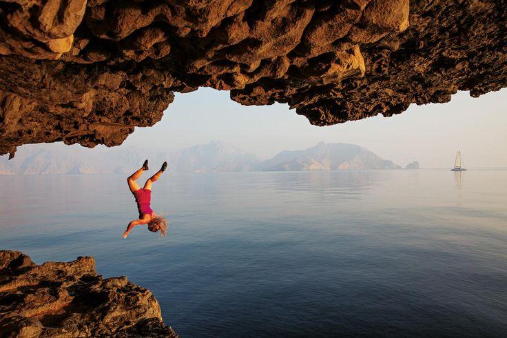 Séance de psicobloc à Oman. Le principe : grimper aussi loin que possible sur la roche puis lâcher prise pour se jeter à l'eau - National Geographic France