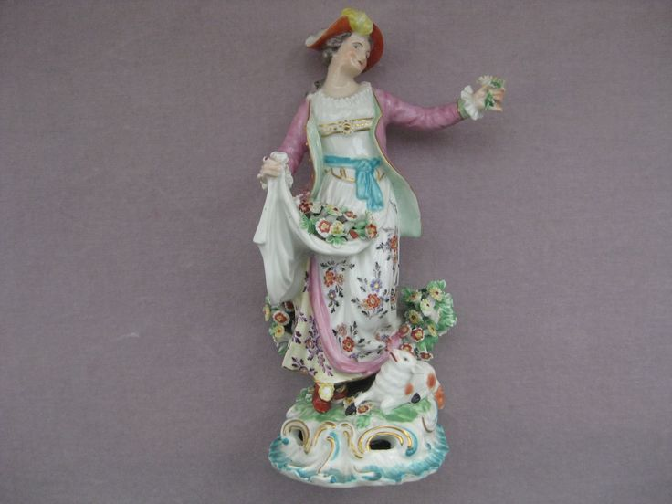 """A  Derby figure of a """" Dresden Shepherdess"""" with a lamb at her feet and her apron full of flowers and  standing on a rococo base. Patch marks  Incised G Circa  1765      Height  7 1/2"""""""