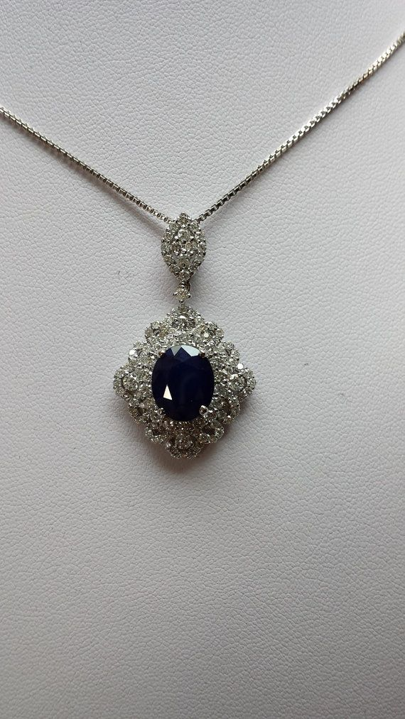 14k white gold pendent center is 5ctw oval lab grown sapphire and 2.50ctw F/G color SI2 clarity diamonds