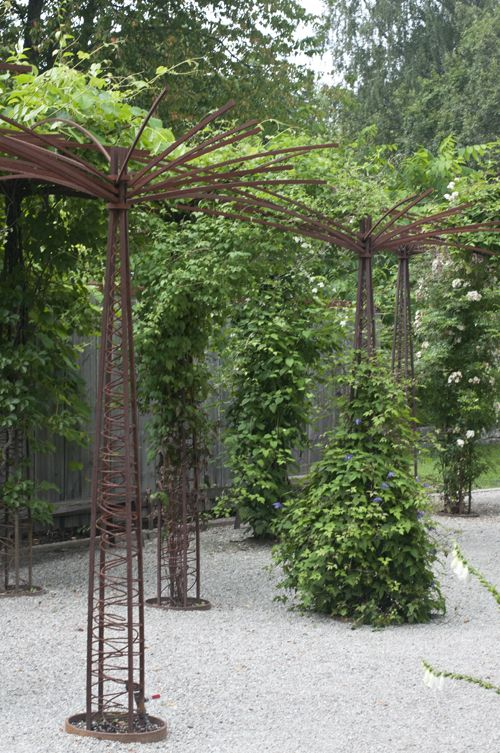 I'm intrigued by the organic yet architectural feel of these metal supports and the overall pergola arrangement.