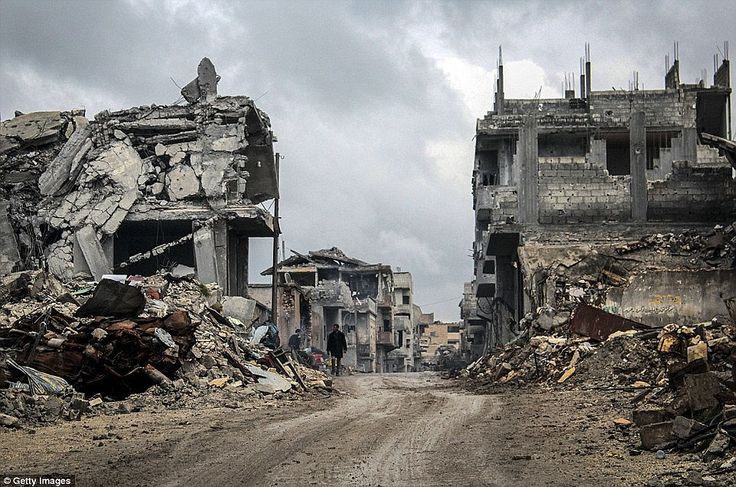 Wrecked: Destroyed buildings are seen lining this road that runs through the centre of the strategic Syrian border town of Kobane