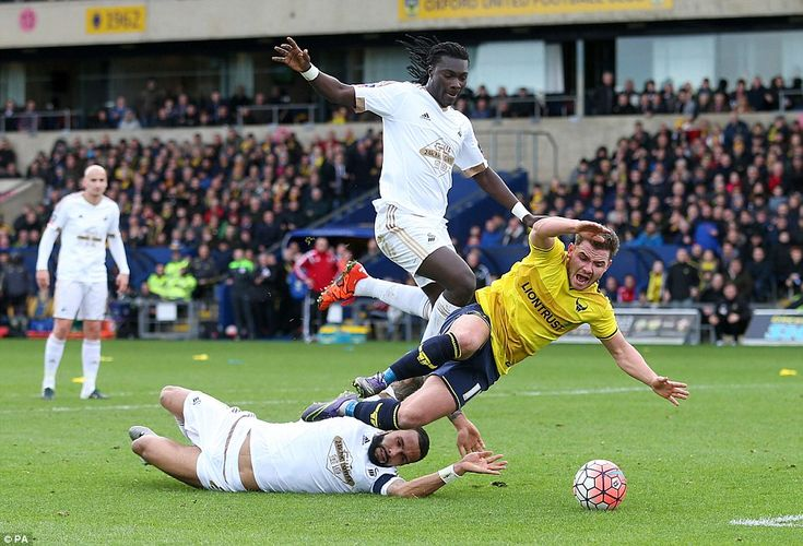 Swansea 2 Oxford 3: Bartley (left) brought down Oxford United's Alexander MacDonald, with the referee quick to point to the penalty spot in the aftermath