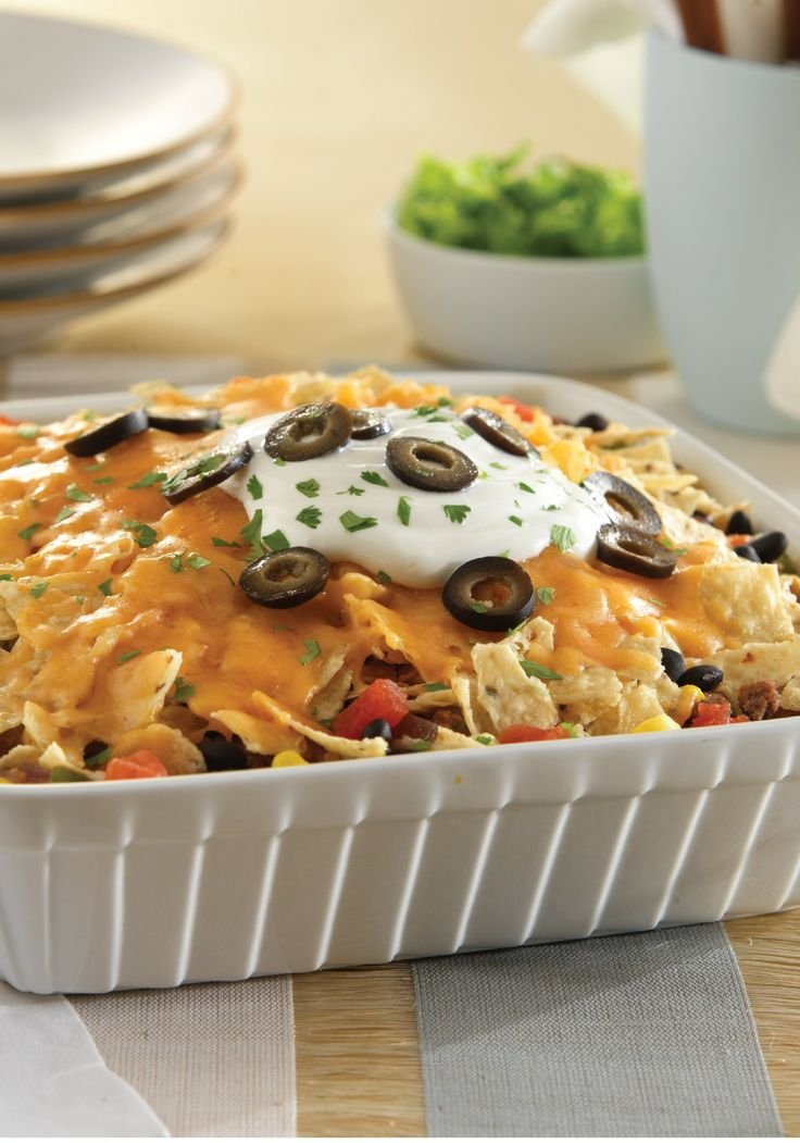 Enjoy the taste of fully loaded nachos layered and baked in this irresistible Baked Nacho Casserole recipe. It makes the perfect summer barbeque dish!