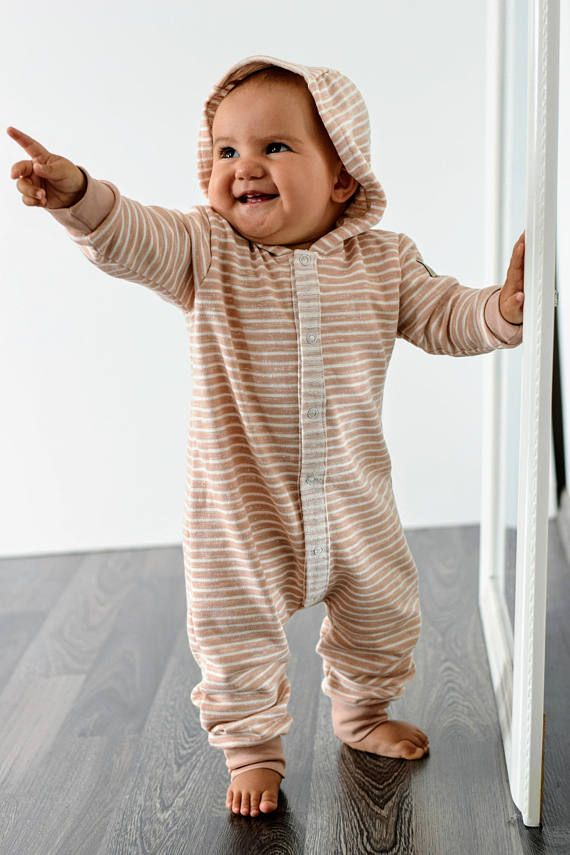 ORGANIC FRENCH TERRY BLUSH AND WHITE STRIPED OVERALL WITH A HOODIE Made from premium GOTS certified French Terry - smooth on the outside with a looped back. The fabric resilient but stretchy and soft too due to its texture. Featuring contrasting front opening with snap fasteners for easy