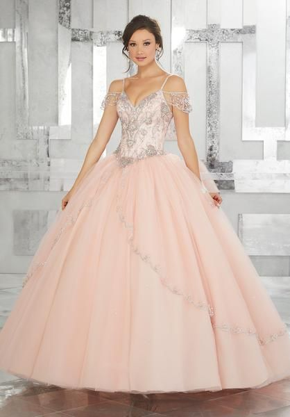 Dramatic and elegant, radiate the room in a Mori Lee Vizcaya Quinceanera Dress Style Number 89135 at your Sweet 15 party. Made out of tulle, this Quince dress features off-the-shoulder cap sleeves top, intricately beaded V-neck bodice, traditional split front A-line skirt, and a lace-up corset back. A matching stole is included.  Colors: Bahama Blue, Black Cherry, Royal Blue, Blush, White  Please allow 4 - 5 months for delivery because Mori Lee Vizcaya Quinceanera dresses are made-to-order…