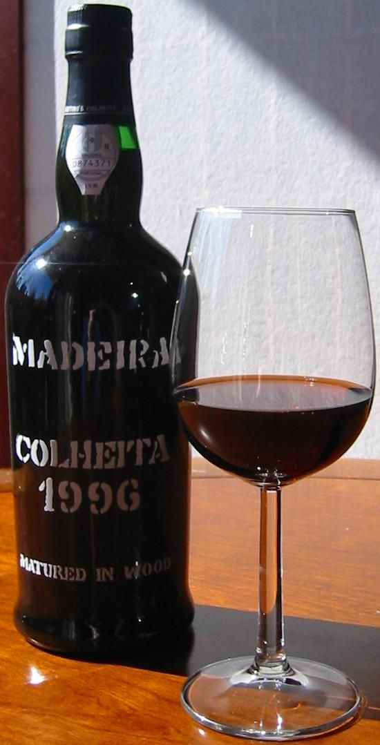 """Glass and bottle of Madeira wine from Vinhos Justino Henriques. Colheita 1996 """"Fine rich"""" (Malvasia) / commons.wikimedia.org 