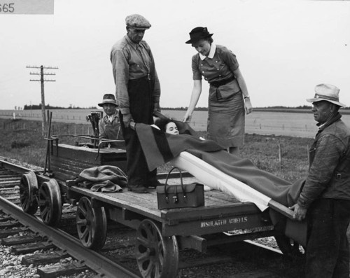 """""""A patient is being transported to hospital from a rural section of Alberta by a railroad speeder under the supervision of a Provincial District Nurse,"""" 1947."""