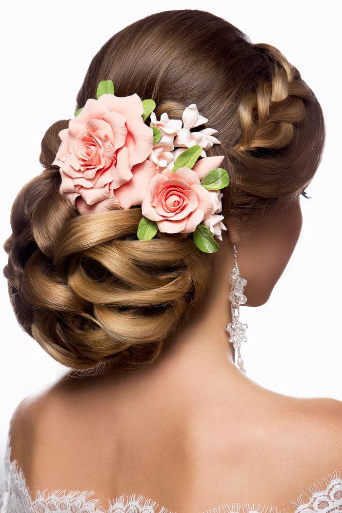 Prachtig bruidskapsel in de vorm van een volle knot met een zijdelings ingevlochten classy touch.