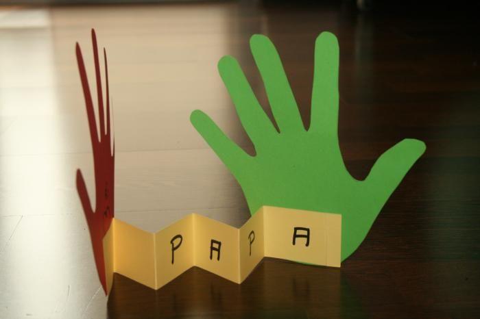"""Teken de handen van je kindje op twee verschillende gekleurde bladen. Knip ze uit. Neem een derde blaadje gekleurd papier en knip er een strookje af. Maak er een """"muizentrapje"""" van en kleef het tussen beide handjes.  Op het strookje kan je bijvoorbeeld """"papa"""" schrijven."""