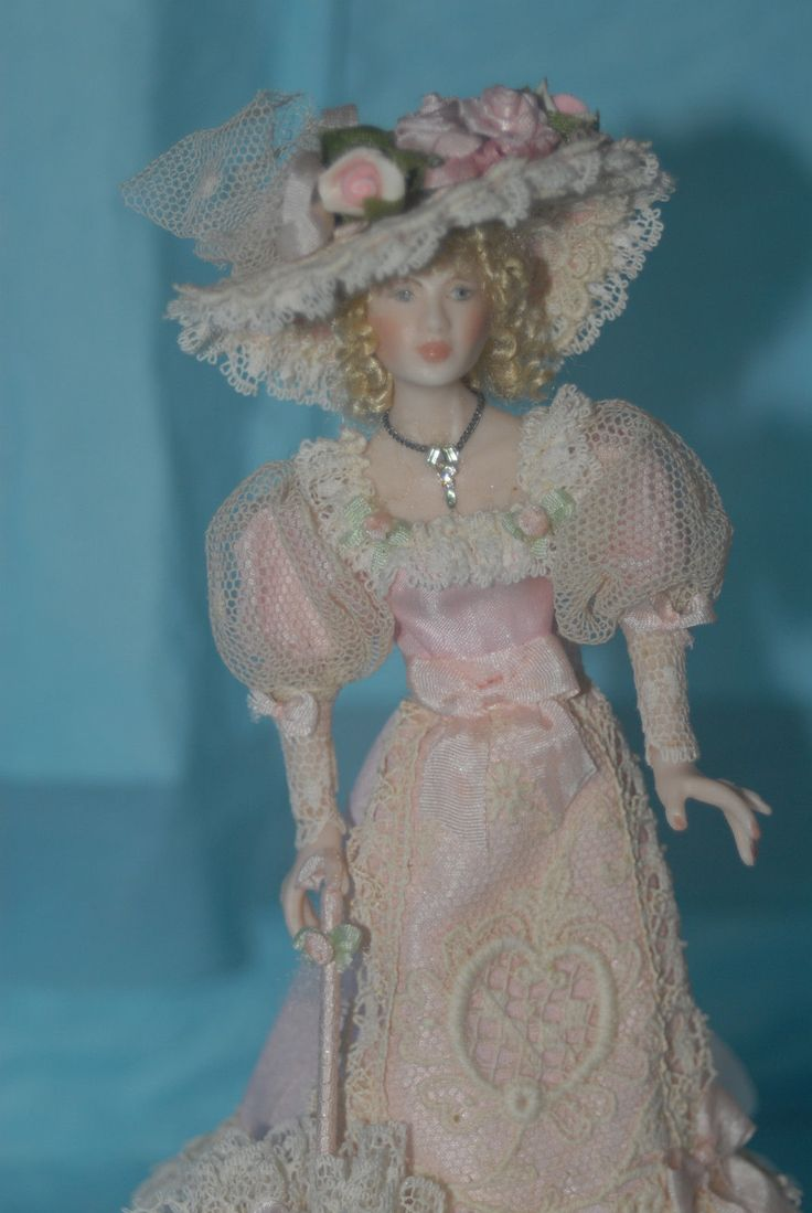 Beryl Nightingale, Clara Cribb Dolls - Victorian woman wearing a pink silk gown that has layers of lace and fabric frills around the hem. The front panel of the skirt is overlaid with lace that is cream color with a heart design.  Around the edges of this panel is another old cream lace trim. The bodice of her dress is trimmed with lace and tiny rosebuds; her sleeves are of old netting, pink bows, and lace. sold on ebay for $56