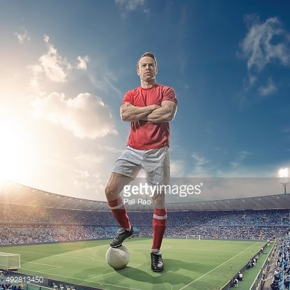 Stock Photo : Giant Footballer Standing in Floodlit Soccer Stadium At Sunset
