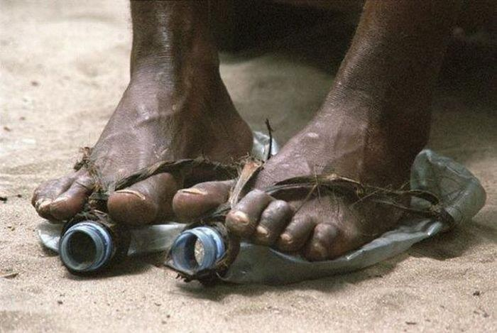 Feet of an African man in shoes made of plastic bottles and bark