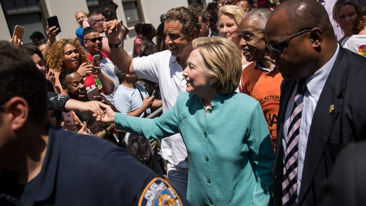 """Hillary Clinton Marches in New York's Gay Pride Parade - - - Hillary Clinton, presumptive Democratic nominee for president, on Sunday marched the final few blocks of New York's annual gay pride parade through throngs of cheering supporters packed along iconic Christopher Street. """"Hillary! Hillary!"""" crowds chanted as she walked slowly to shake hands and pose for photos, flanked by New York Governor Andrew Cuomo and New York City Mayor Bill de Blasio.  --  June 26, 2016 -  Bloomberg Politics"""
