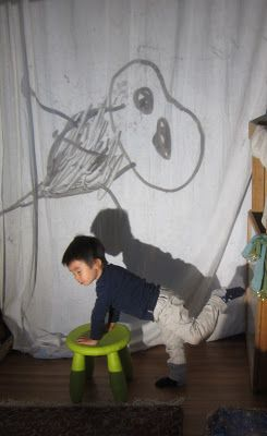 Figure Drawing - Larger than Life: Children do their figure drawing on the light projector while their friend posed in front of the curtain, and others drew on their drawing boards.