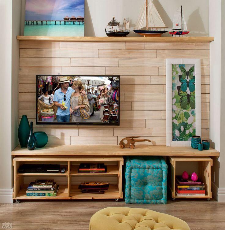 Olha que legal essa composição para a área da TV! Ele delimita uma área entre a prateleira e o rack e diferencia através de um revestimento de tom neutro e que traz um padrão de retângulos horizontais. Bem bacanoso!