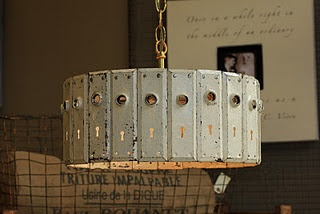 Article in link contains 25 Ways to repurpose Old doors - example shown is a light fixture made from old door plates.