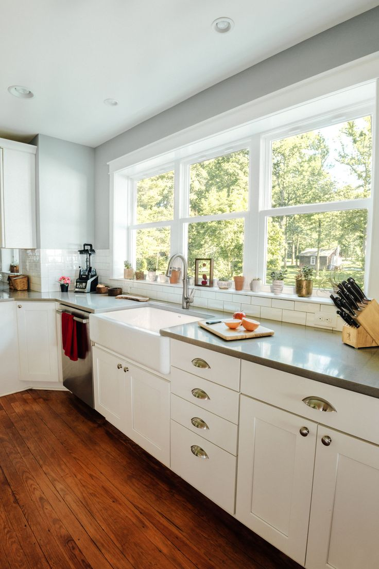 This farmhouse sink, subway tile back splash, and natural hardwood floors combine to create such an inviting look!