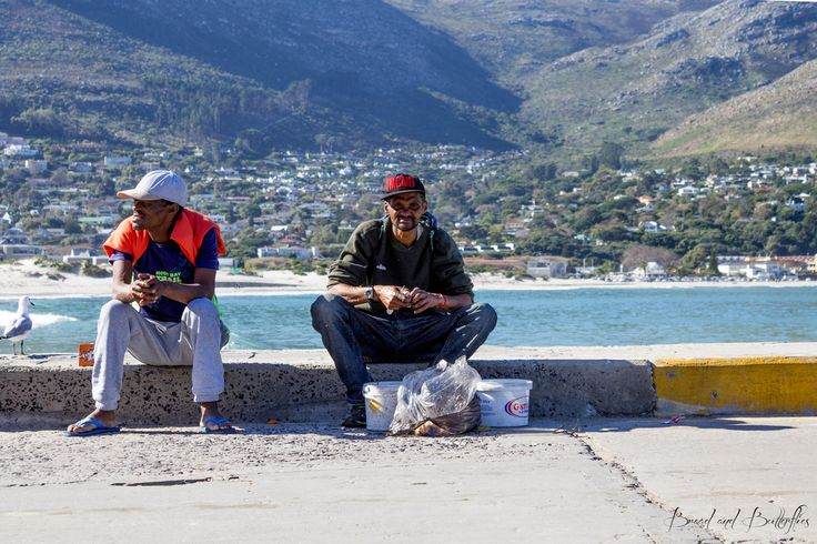 Cape Town fishermen at Hout Bay Harbor on a lazy Sunday afternoon.