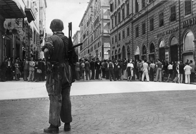 Once allies, now enemies: A German paratrooper stands guard outside the Italian Ministry of Internal Affairs in Rome after Italy capitulated in September 1943