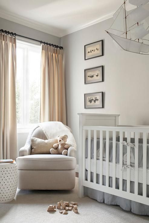Sweet boy's nursery features a ship mobile hanging over a white traditional crib dressed in white ...