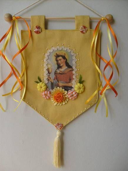 Estandarte Santa Bárbara <br>Feito em tecido , com fitas e flores <br>Produto artesanal , sujeito á variações <br>Podemos fazer com outros motivos religiosos <br>Temos vários modelos <br>Consulte - nos