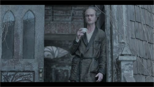 This image, obtained from the files of the Netflix corporation, shows Count Olaf drinking a cup of coffee while the Baudelaires chop wood.