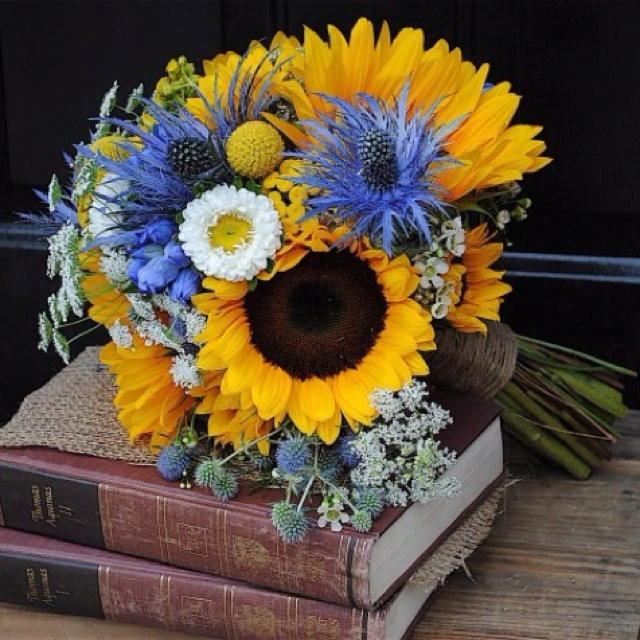 Pretty yellow and blue bouquet of sunflowers, thistle, asters, scabiosa, and seeded eucalyptus.