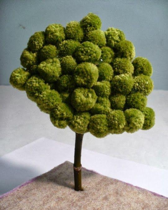 Uma nini árvore feita com um ramo e pompons de lã verde! FULL TUTORIAL HERE via Dollar Store Crafts po...