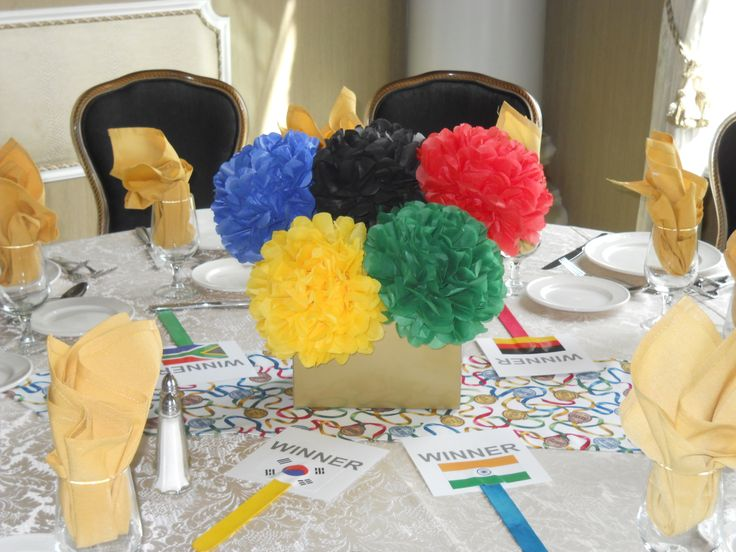 5 tissue paper flowers in olympic ring colors inside a gold box. Table runner made of medal fabric and winner wavers with olympic picograms and country flags. All for the a centerpiece for a school Go For The Gold tricky tray.