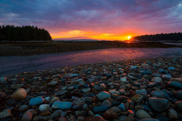 Sunset over Acadia National Park's shoreline casts orange light on rocks in the foreground.