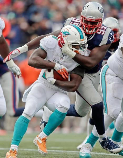 New England Patriots defensive ends Chandler Jones (95) wraps up Miami Dolphins running back Lamar Miller