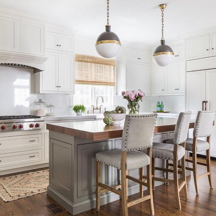 A pair of Hicks Pendants hang over a gray paneled kitchen island topped with thick butcher block ...