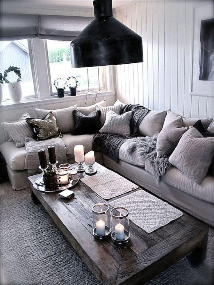 O sofá em L foi preenchido com inúmeras almofadas e mantas nesta sala de tons neutros. No piso, tapete quentinho e, na mesa de centro, velas completam o decór.