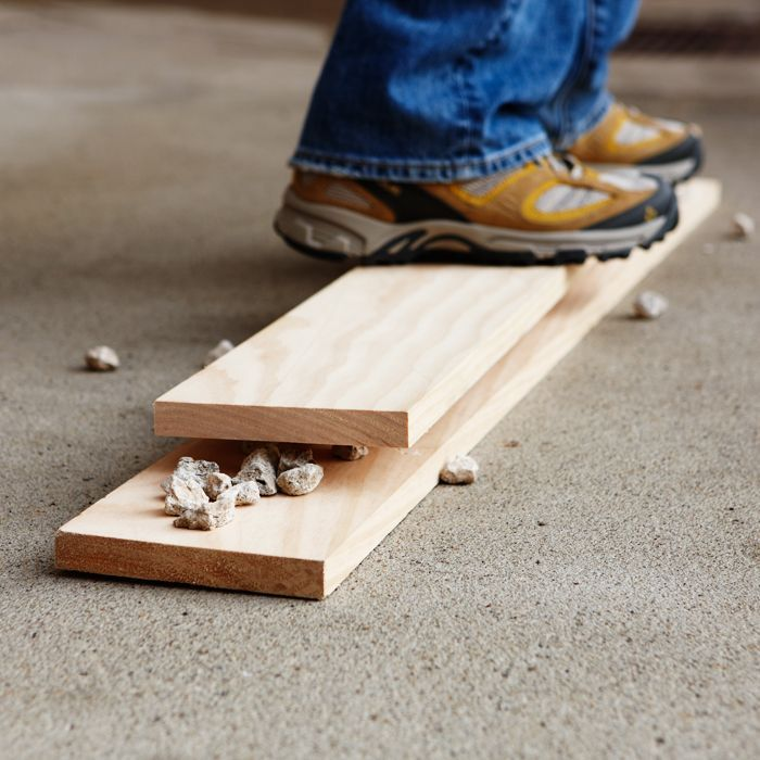 Lay a second board on top of the gravel and stand on it to distress the gravel