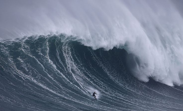 Big-wave surfer Sebastian Steudtner of Germany drops in on a large wave at Praia do Norte in Nazare, Portugal, on November 1, 2015.