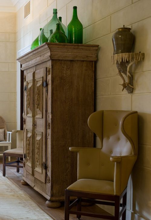 Decorating on top of an armoire: use large simple accessories. (artificial plants don't add anything) Sometimes we decorate on top of an armoire, and sometimes not. But, when we do put something here, it is a select group of sturdy objects.