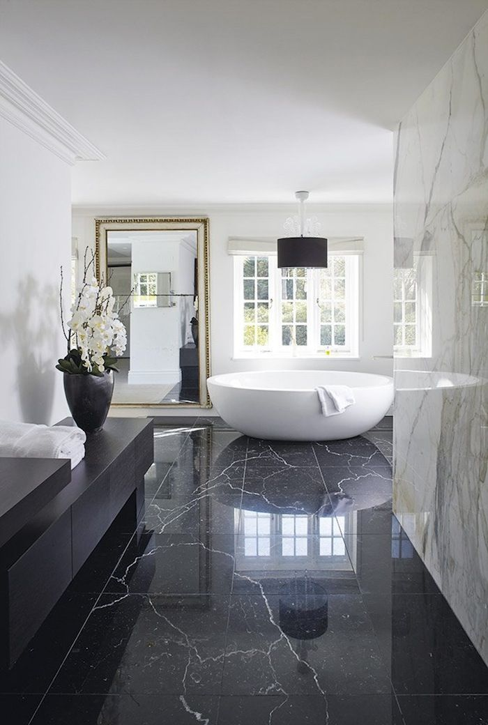 Wow factor, glam, sophisticated, luxe, marble bathroom with freestanding  bath and black marble floor tiles.