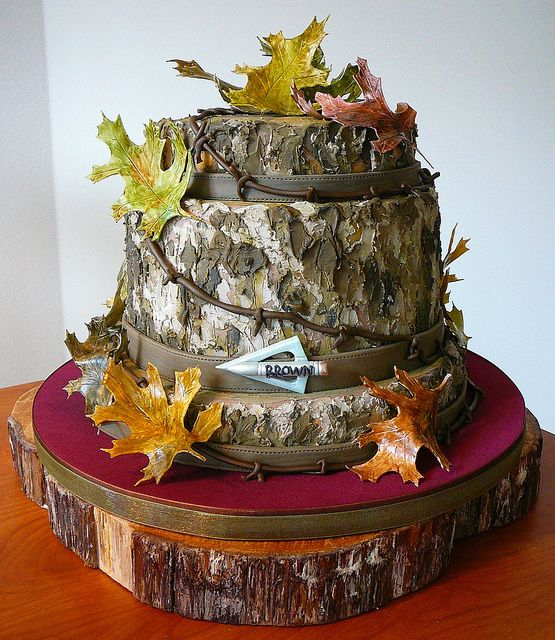 Groom's Mossy Oak Motif Cake: Cut Wood Rounds, leather belt, broadhead arrowpoint with groom's name; barbed wire and falling leaves; Chocolate Sour Cream Cake with Butter Pecan Buttercream and milk chocolate fondant