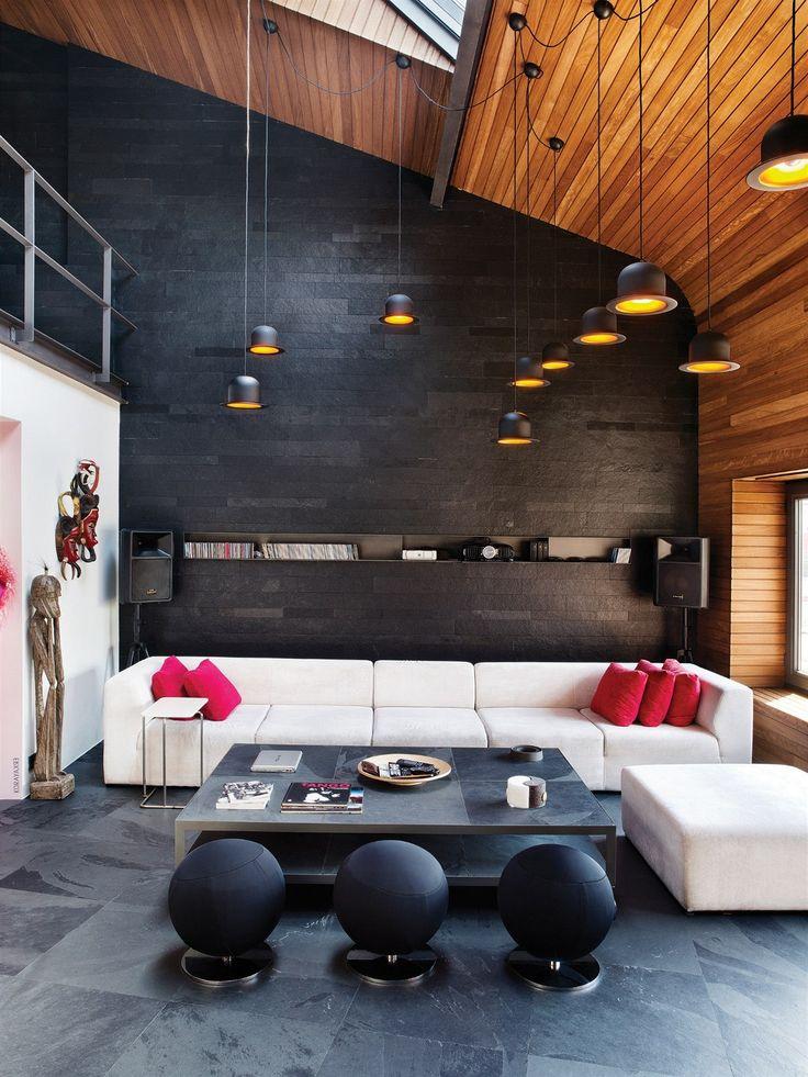 Důstojným protipólem ke stěně zahlcené nejrůznějšími věcmi je hladká plocha stěny obložená panely tmavého přírodního kamene.