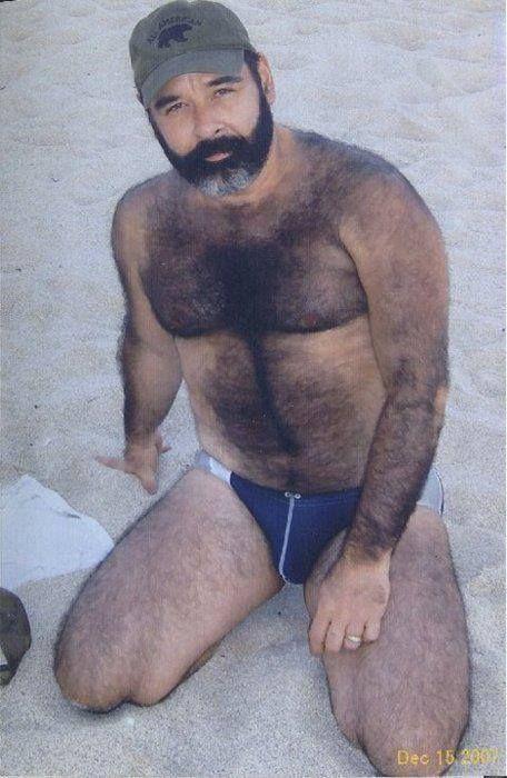 Very hairy black bearded man in a Speedo