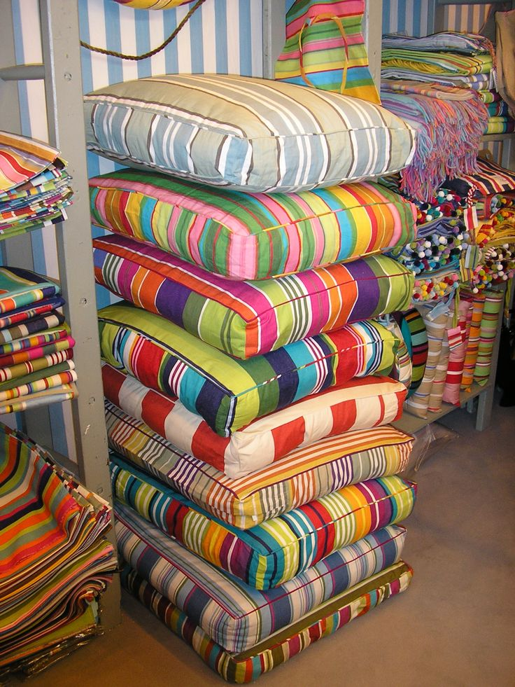 Colorful Floor Cushions Stacked On The Side Of The Porch