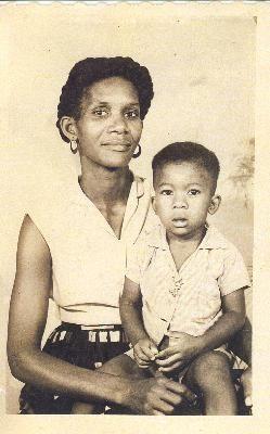 1963, Suriname, Paramaribo Op deze foto zie je mijn moeder met mijn broertje Alwin. Mijn moeder had vijf kinderen. Ik was de oudste dochter en deze broer verschilt zes jaar met mij. Mijn moeder kwam zelf uit een gezin van acht kinderen. Mijn oma was ook alleenstaand en kreeg het financieel niet rond om voor alle kinderen te zorgen, en zodoende werd mijn moeder grootgebracht in een Duits kindertehuis.
