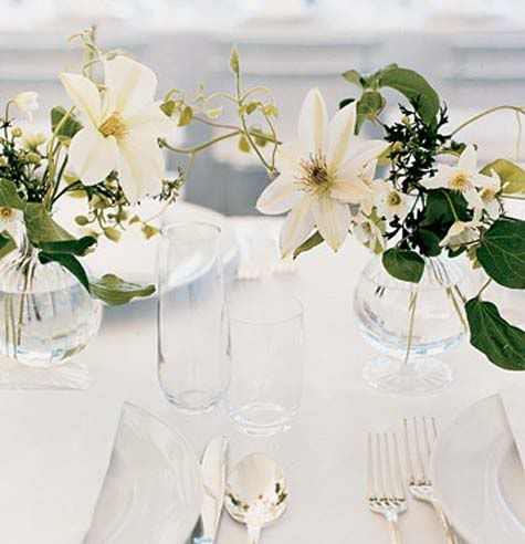 Small vases tucked among the larger pieces on the long reception tables