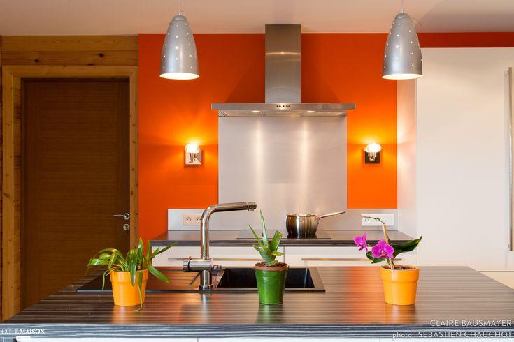 Cuisine au mur orangé, design. Inox. Peu d'élements décoratifs, pour une pièce design et épuré.